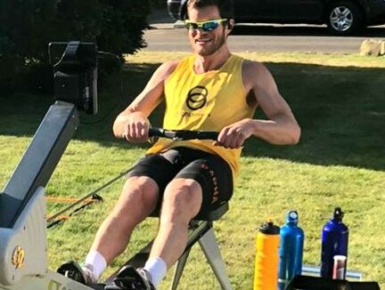 A man wearing a Sightsavers T-shirt rows outside on a rowing machine in a sunny garden.