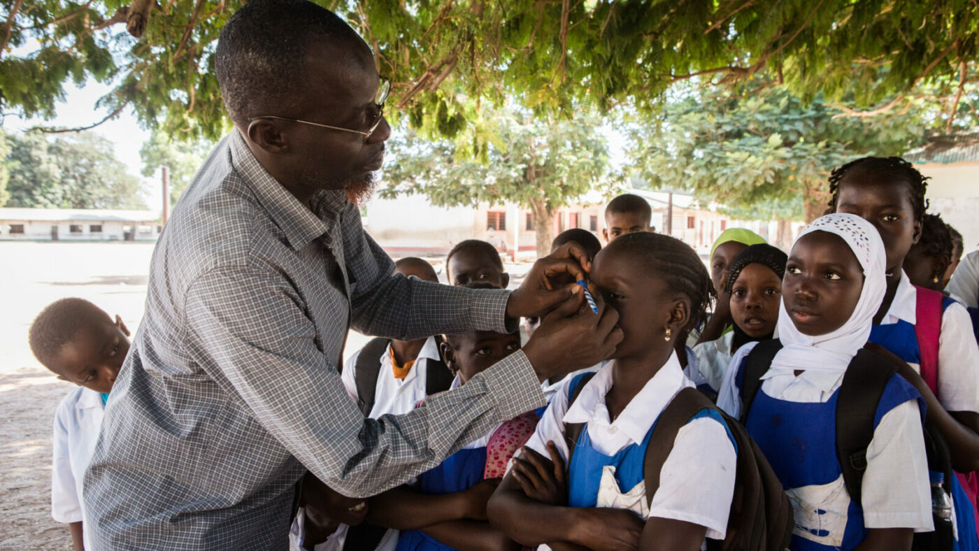 A health worker checks childrens' eyes for signs of trachoma.