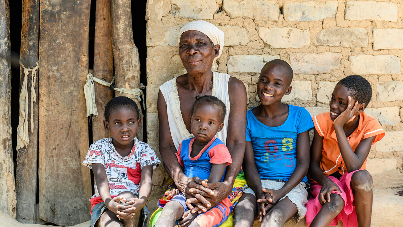 A woman sits with her four grandchildren.