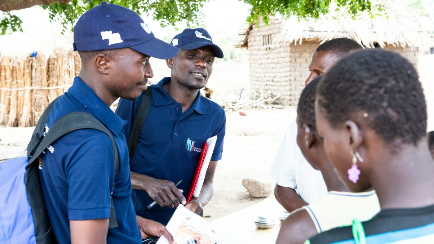 Two men wearing dark blue uniforms hand out paper surveys to a group of people.