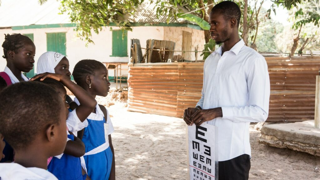 A man talking to children outside. He holds an eye chart.