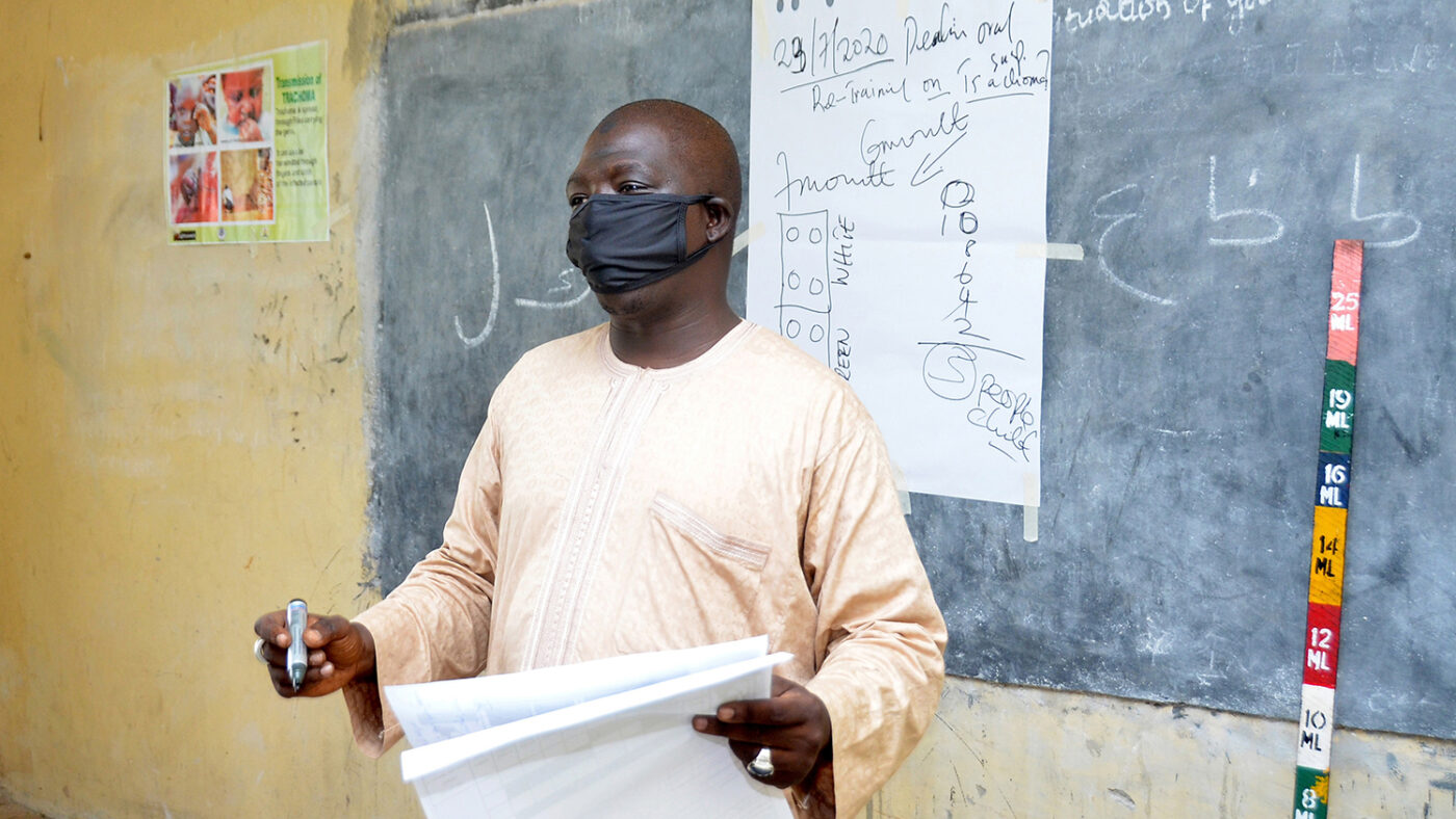 A man, wearing a mask, presents in front of a chalk board during a training.