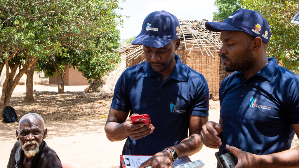 Two community volunteers enter patient information into a mobile phone.