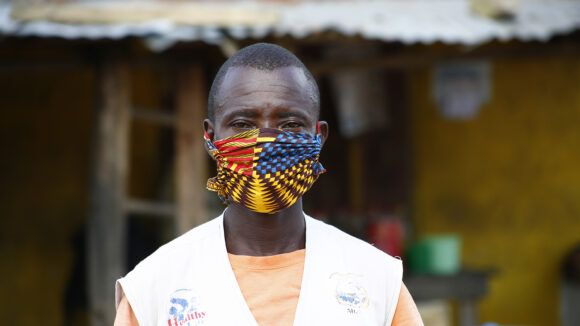 A male healthcare worker stands outside wearing a colourful face mask and a white coat.