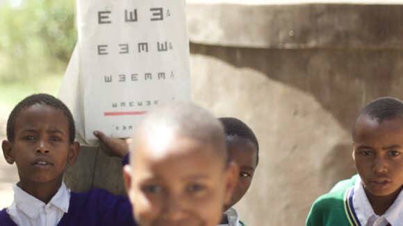 A group of children stand near an eye chart,.