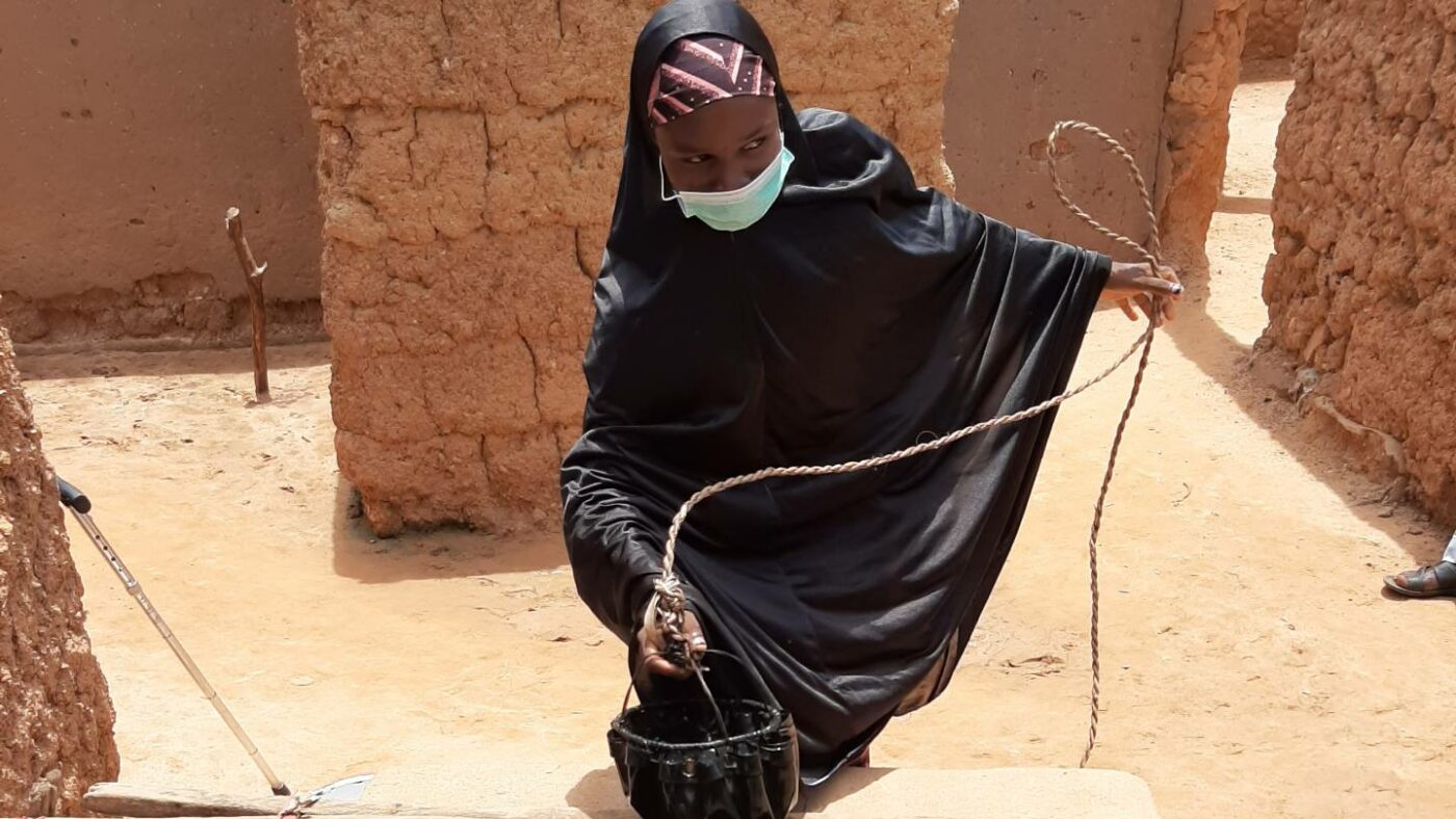 A young woman uses a rope to pull a small vessel of water up from a well.