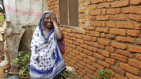 Amina covers one eye with her hand and smiles after cataract surgery.
