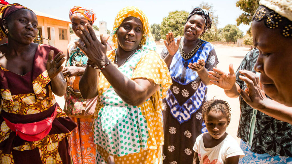 A group of women sing, dance, and clap their hands.