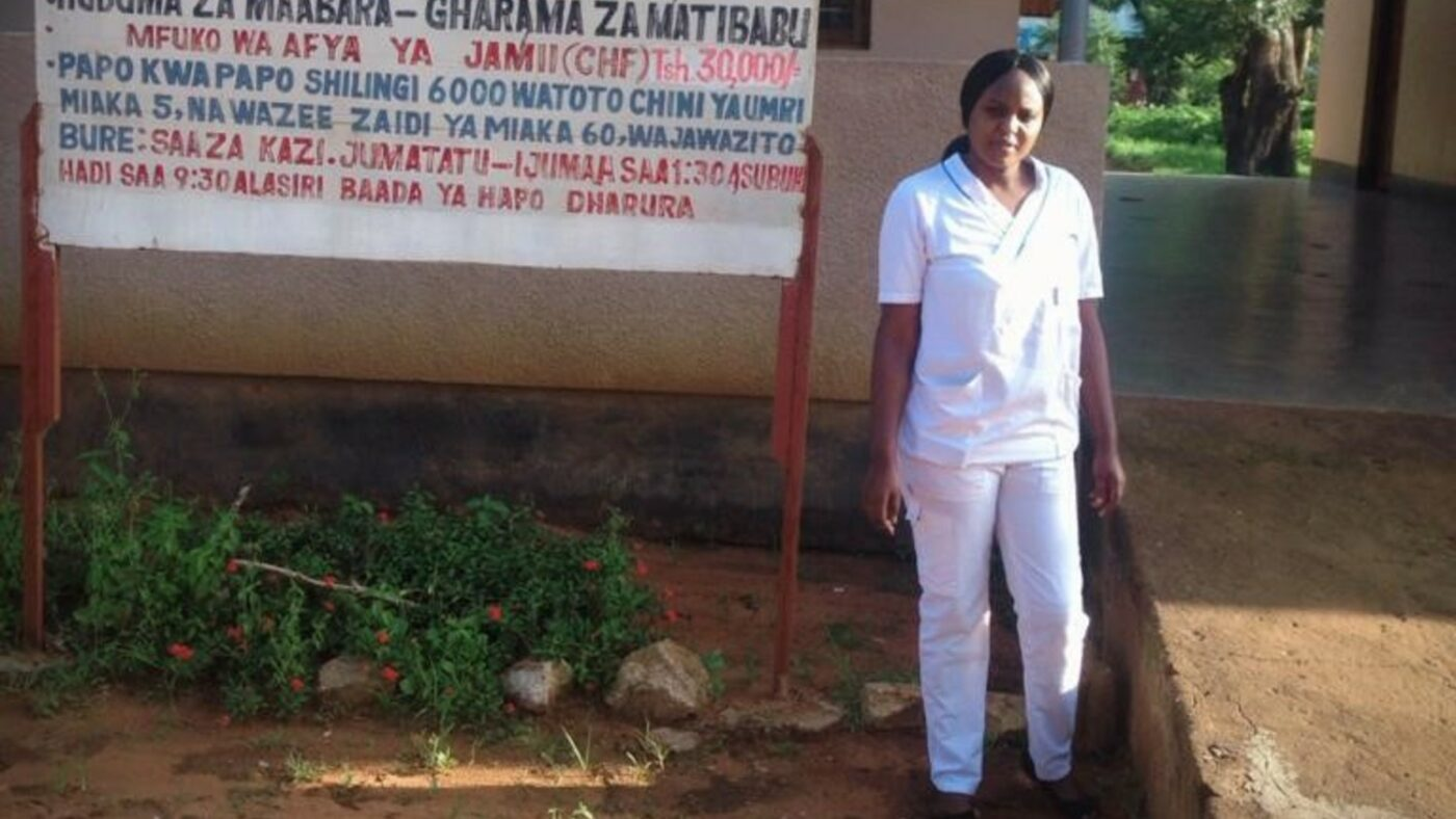 A nurse stands outside a hospital in Tanzania.