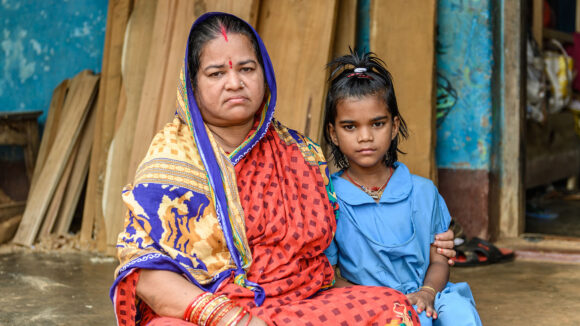 Archana sits with her grandmother. Grandmother has her arm round Archana.