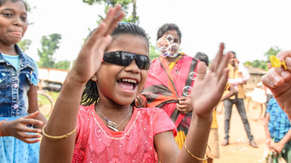 Archana is wearing protective glasses and happily chasing bubbles.