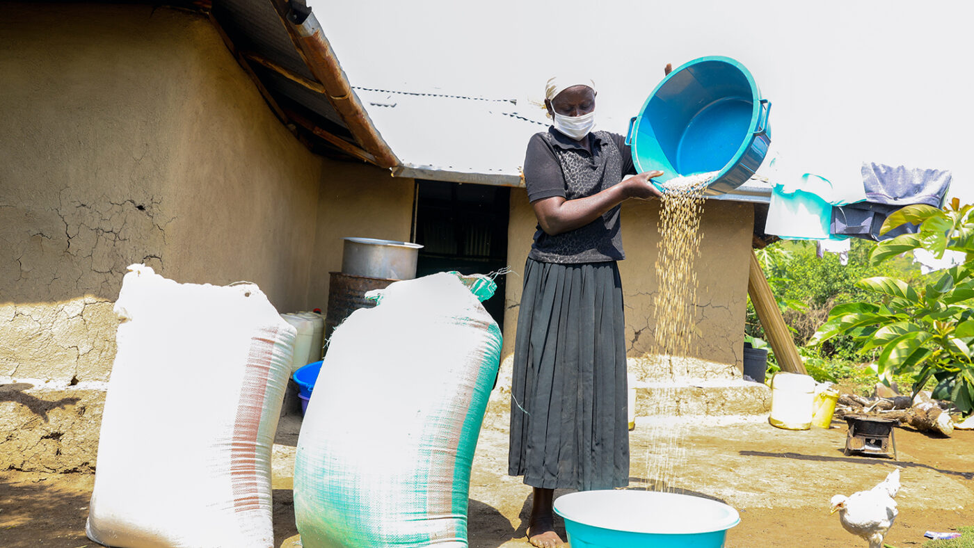Hellen Odero pours grain from a bowl outside her home.