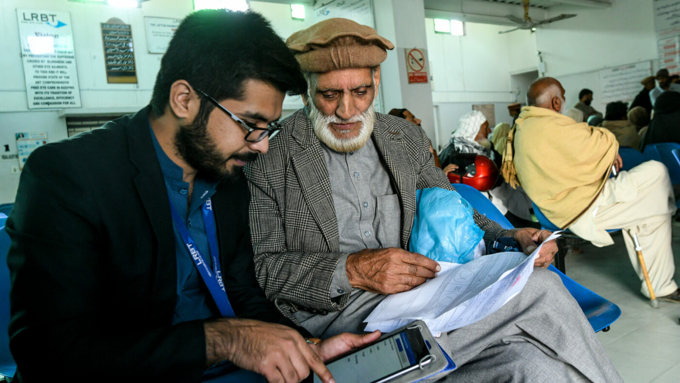 An older man talks to a younger man, who is holding a tablet computer. They are sitting in a hospital waiting room.