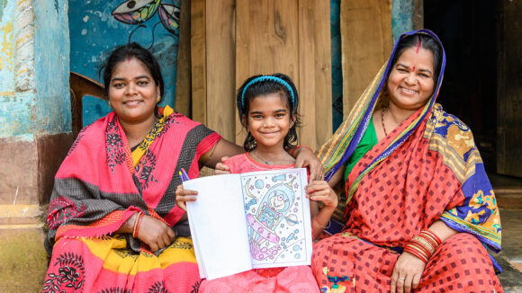 Archana with her family looking happy sat outside their home.