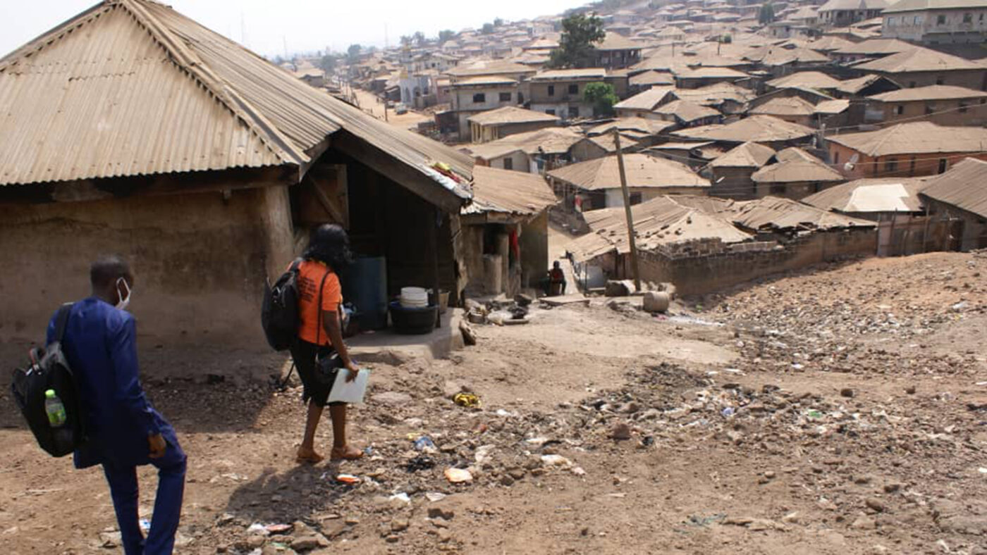 A steep dusty road flanked by huts on each side.