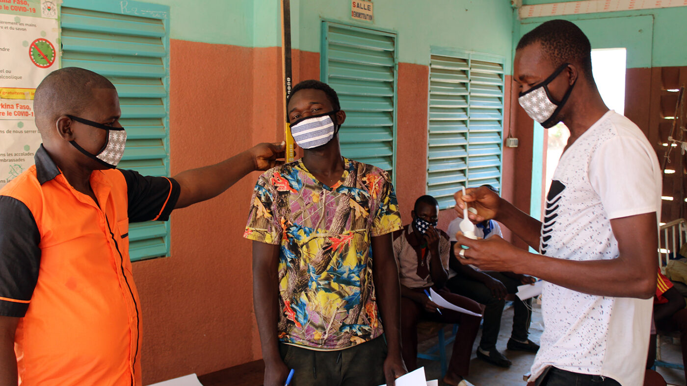 Two volunteers in masks are shown by a trainer how to measure a patient's height.
