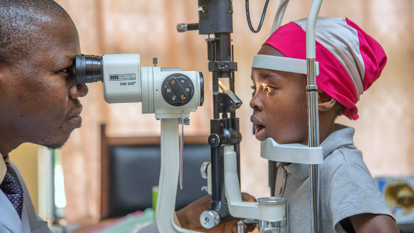 A young girl has her eyes checked by an eye specialist.