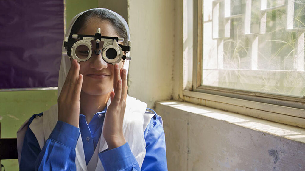 A girl smiles as she has her eyes tested.