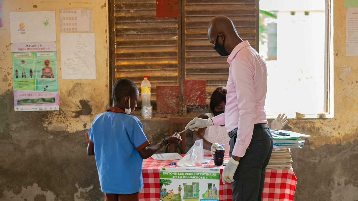 A school student is handed a tablet by the head teacher.