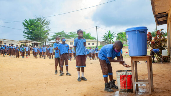 School children in Cameroon line up to wash their hands from a large bucket.