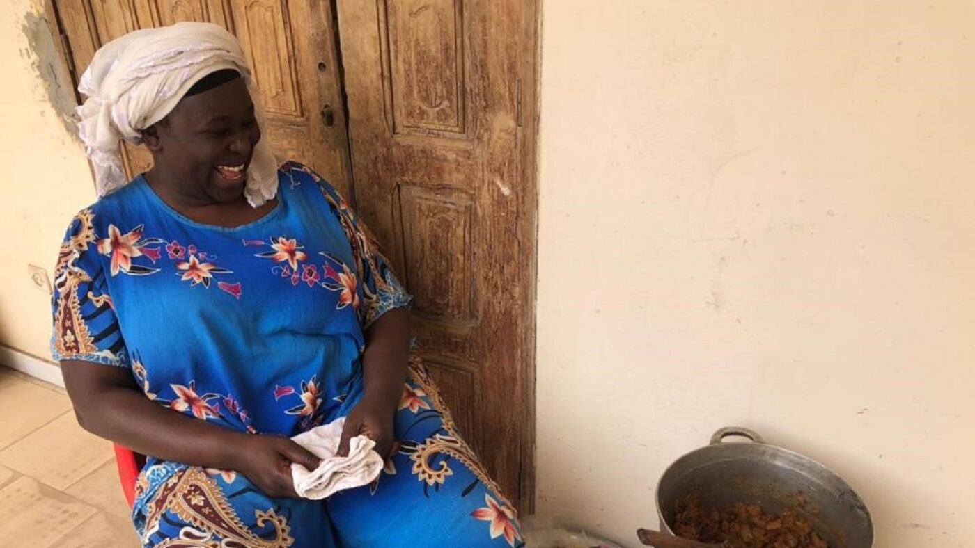 A lady smiles, sitting next to a cooking pot