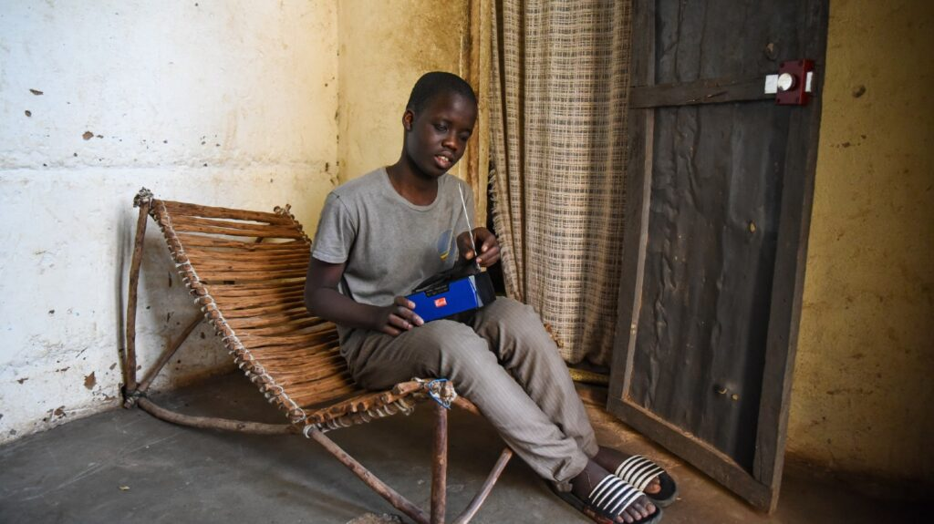 A young boy sits in a wooden chair at home, holding a radio.