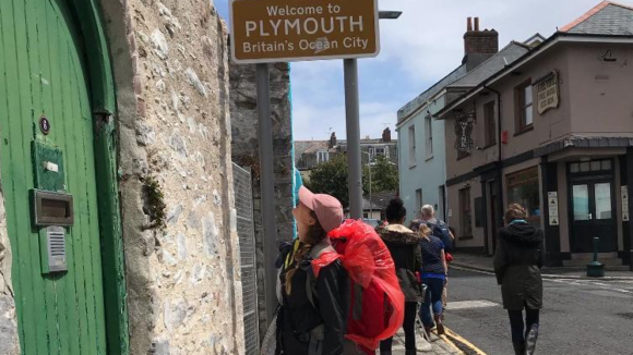 A young woman, Lily, stares up at a sign saying 'Welcome to PLymouth' while wearing a cap and large rucksack.