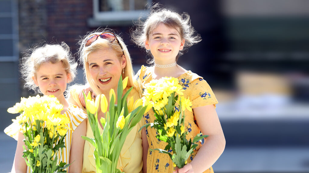 A woman and two children smile in the sunshine. They're all wearing yellow clothing and holding yellow flowers.