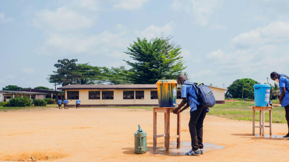Two school children in Cameroon wash their hands outdoors using water rom a large bucket on a table.