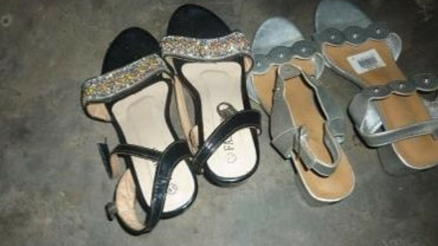 Two pairs of open-toed women's shoes lie on a stone floor. One pair is black, while the other is grey.
