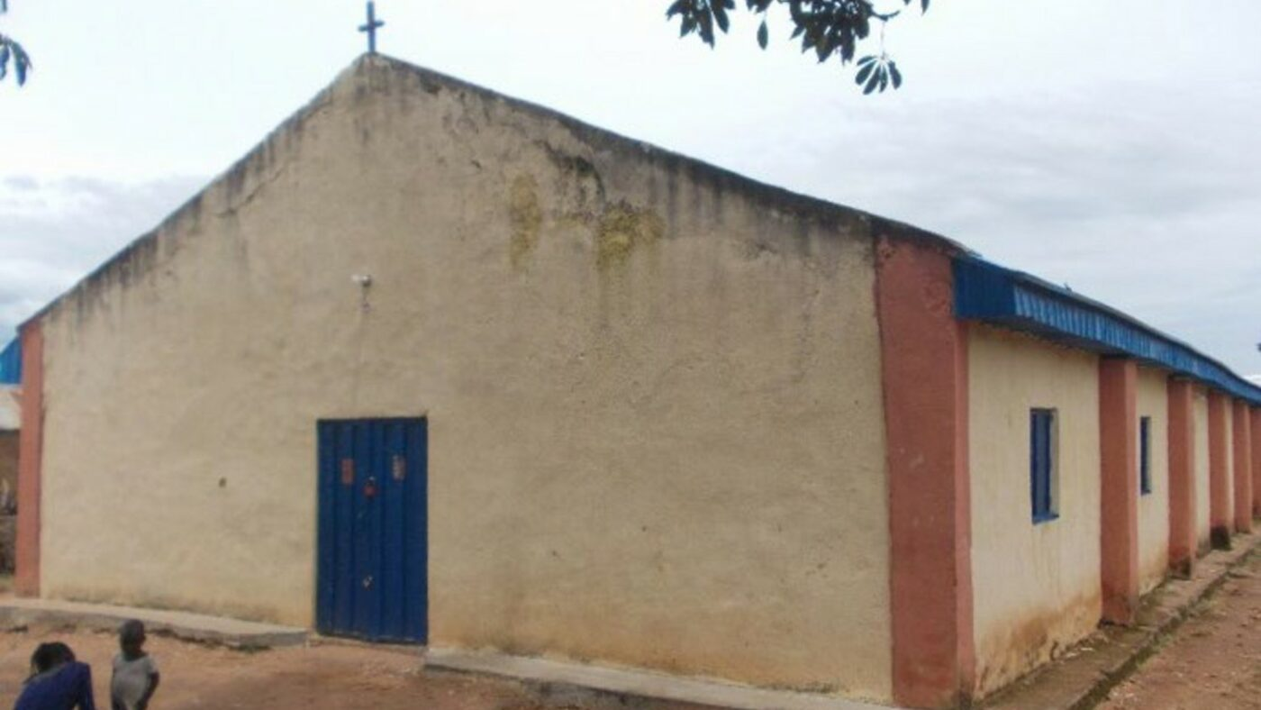 Pictured is a single-storey church building, with brown walls and blue doors and windows. On the church roof there is a small cross.