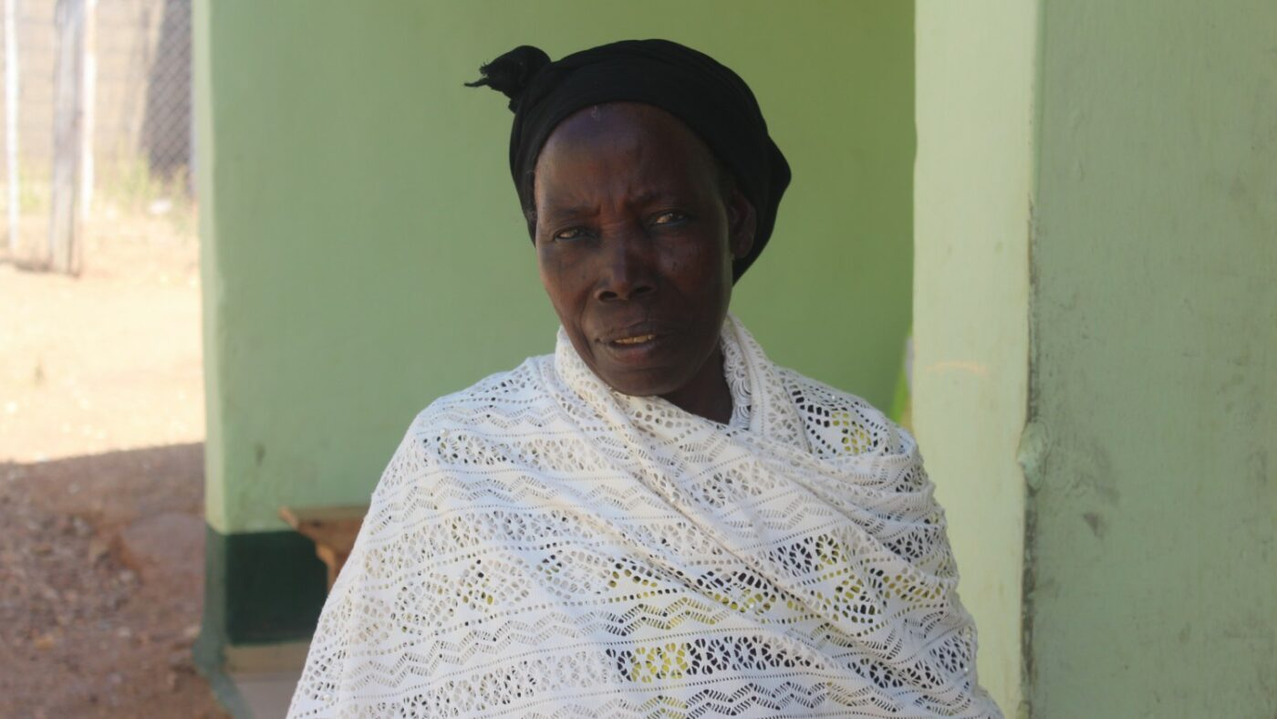 A woman, wearing a black headscarf and a white shawl, looks into the camera.