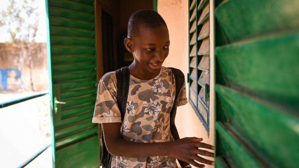 A young boy with a backpack walking through the corridor at school in Mali.
