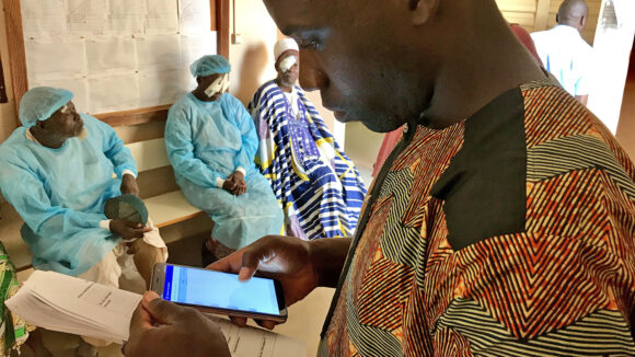 An eye health worker using a mobile phone to record data, with patients in the background.
