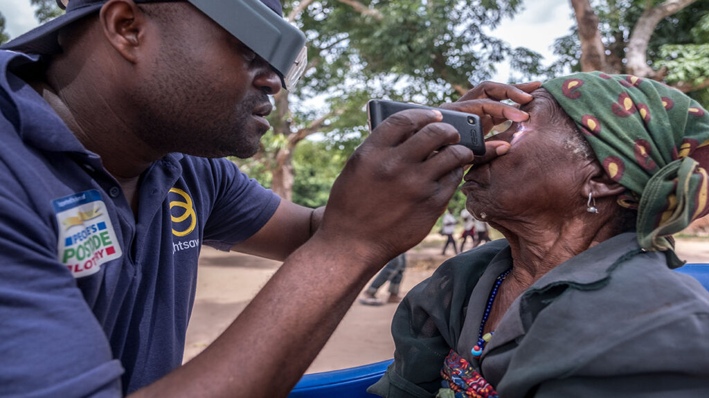 Mai Mai checks a woman's eyes for signs of eye disease.