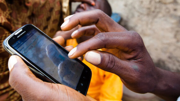 A close-up of a mobile phone being used by a health worker to record data.