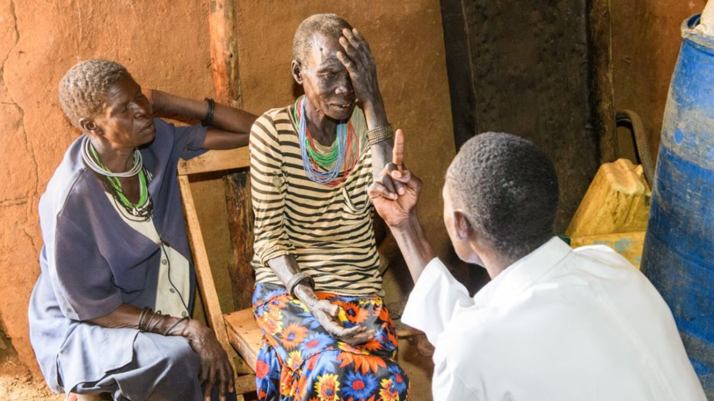An elderly woman sits in a chair, and receives an eye examination from a man wearing a white shirt. Another woman wearing a blue nurse's uniform sits next to her.