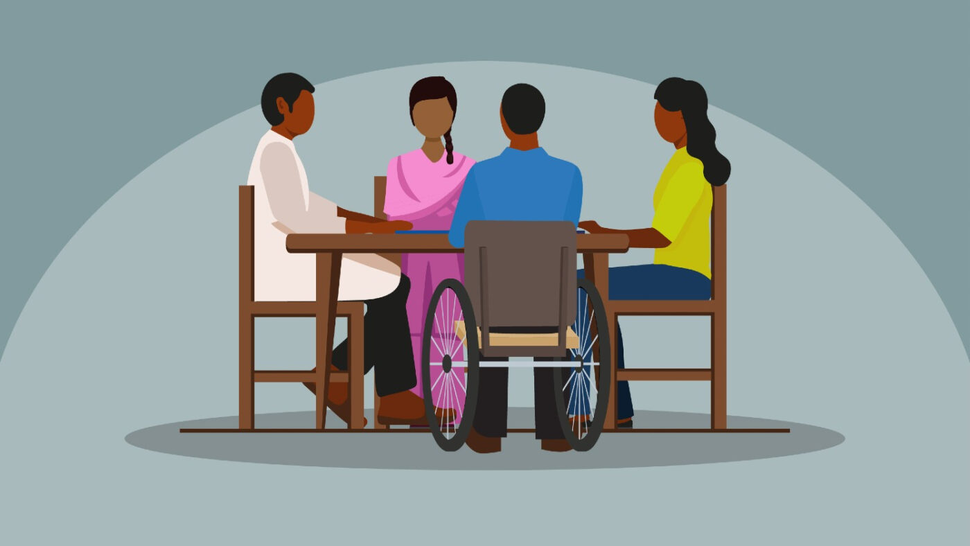 An illustration showing a group of people sitting at a table, talking together. One person in the group is a wheelchair user.