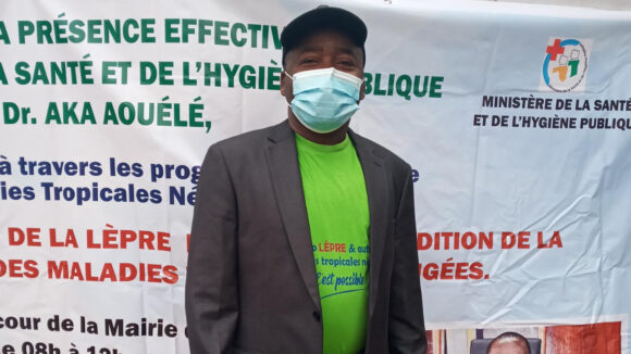 Sightsavers Konan Nguessan stands in front of an event sign written in French.