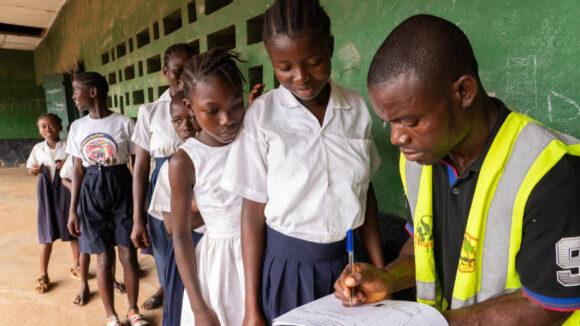 School children in a queue have their information taken by a man