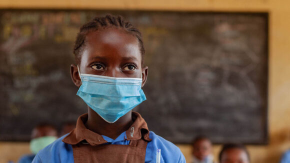 A girl wearing a face mask in a classroom.