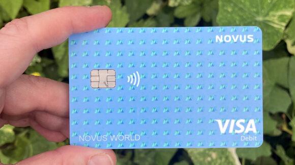 A hand holding a blue Novus bank card, featuring the text Visa and Novus World.