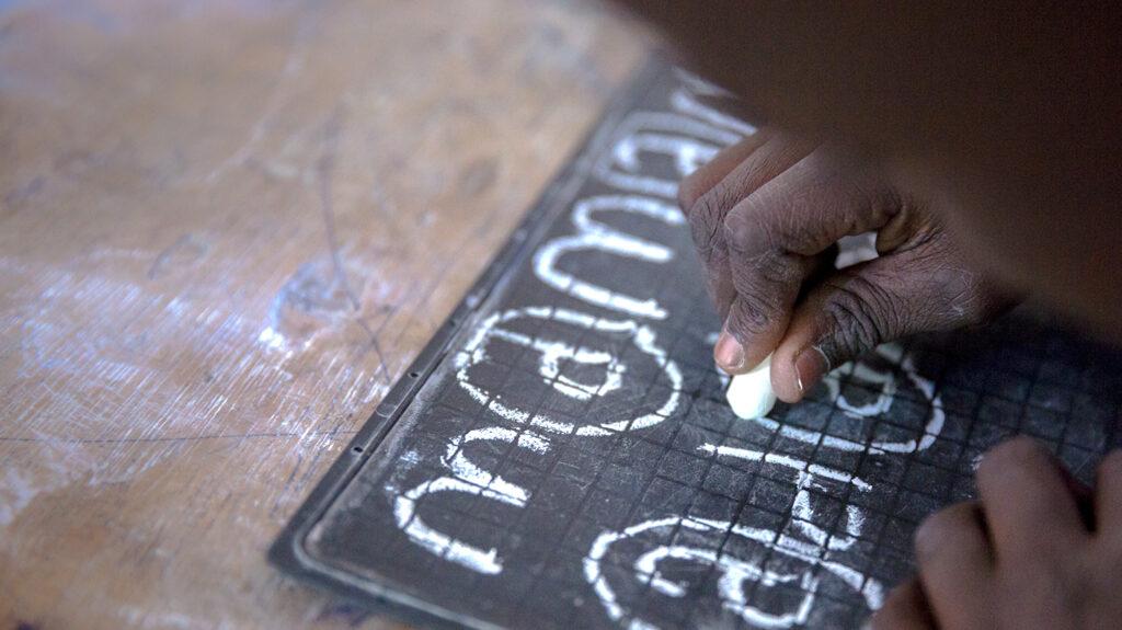 A boy using chalk to write on a slate.