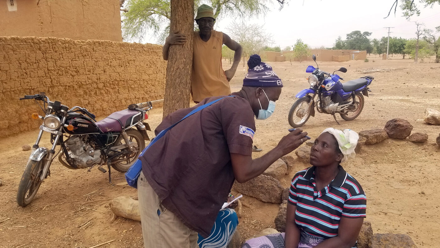 An eye health worker checks the eyes of a woman sitting on a low wall in a dusty setting.