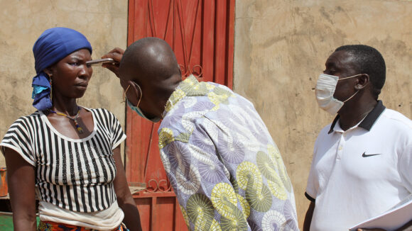 An eye health worker wearing a mask shines a light into a woman's eyes to check for signs of trachoma. Another eye health worker stands nearby.