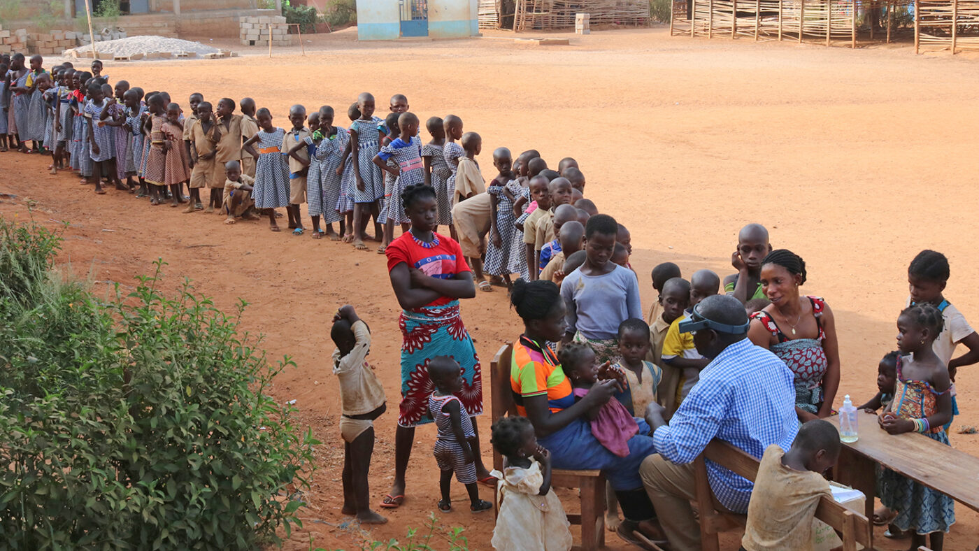 A long line of children queue to see an eye health worker.