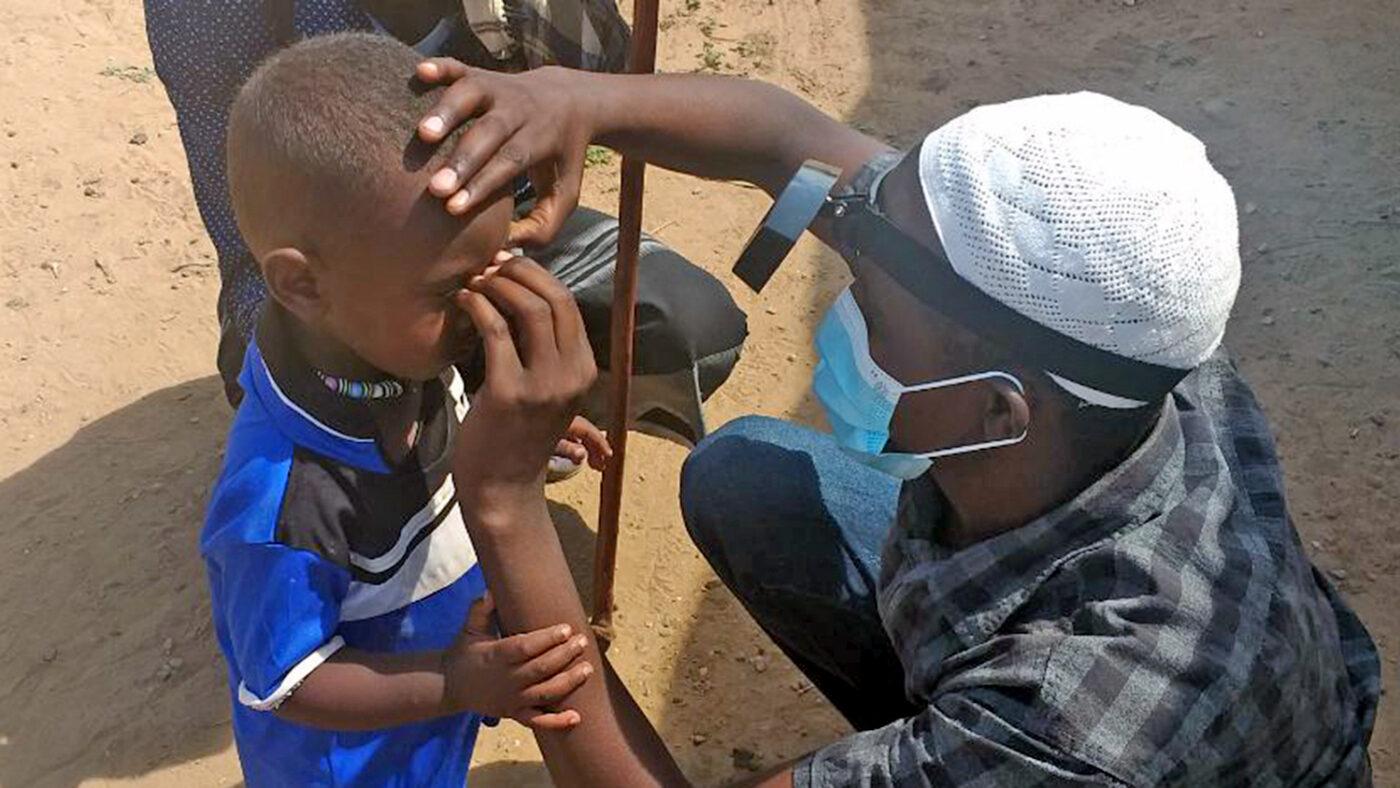 An eye health worker wearing a mask checks a boy's eyes.