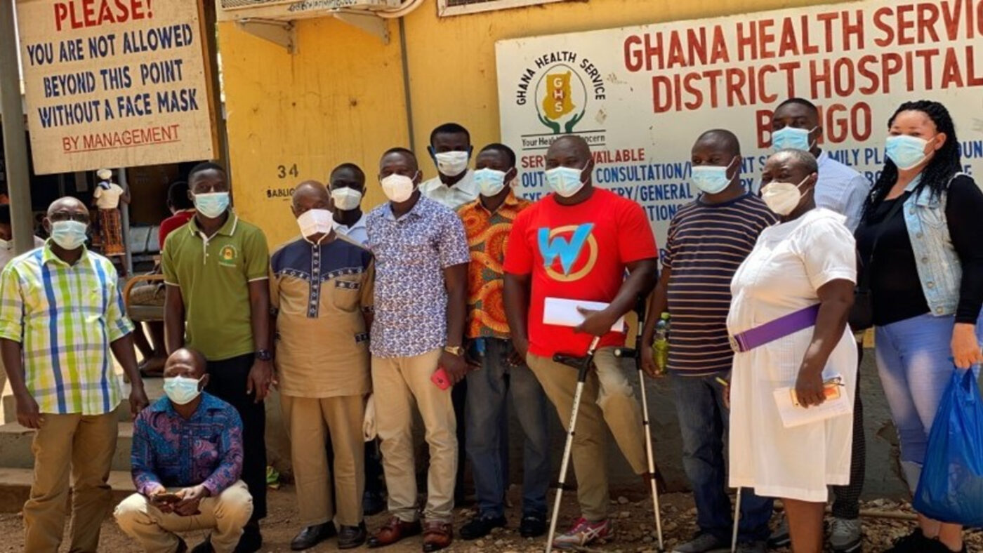 A group of people wearing face masks stand outside a hospital in Bongo, Ghana.