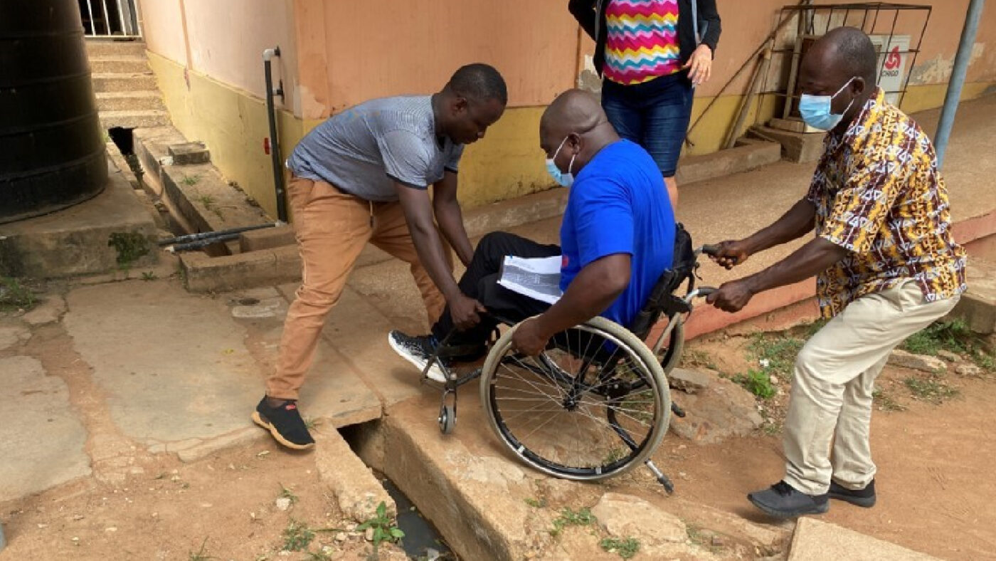 Three men, including one wheelchair user, navigate uneven terrain in the hospital grounds