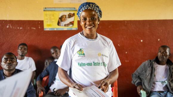 Philomene, a volunteer community-directed distributor, stands smiling inside Massangam hospital